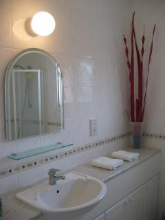 Pristine fully tiled bathroom with a bath and shower screen. Ample storage. Bathroom has a window.