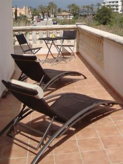 Balcony on first floor with sun beds and tea table set.