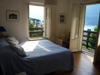 The master bedroom with balcony and view of the lake on two sides