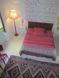 Blue bedroom: kingsize bed, Turkish kilim, curtain of lights, seen from den.