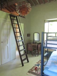 Green bedroom: bunk beds and ladder to den with reading corner and books.