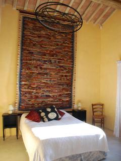 Yellow bedroom: Moroccan kilim above kingsize bed, sculptural Artemide light (dimmable).