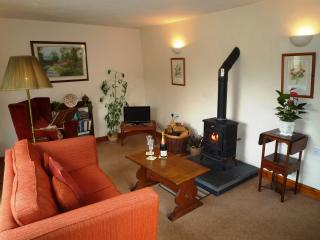 The sitting room has a log-burning stove, comfortable seating, Freeview TV and reading lamp & stand