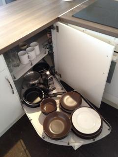 Contents of one of the kitchen cupboards showing ample utensils, cutlery and crockery
