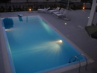 The pool and patio lit up in the evening
