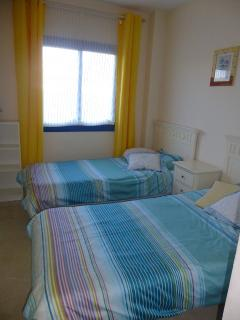The second bedroom features two comfortable single beds.