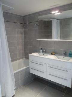 The light and spacious bathroom- the sink and bath / shower unit