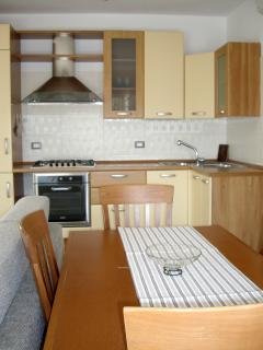 Kitchenette is in a bright living area. Extendable dining table.