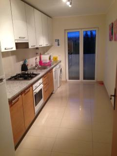 Fully fitted kitchen with doors leading to small rear balconey.