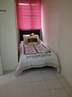 4th bedroom with table fan, single bed, laundry basket