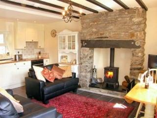 Well appointed lounge with inglenook fireplace housing the multi fuel wood burning stove