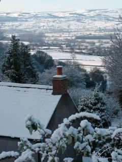 a wintry scene taken from behind the cottage with Denbigh in the distance