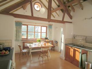 the oak-beamed kitchen, table set for lunch, overlooking the garden.