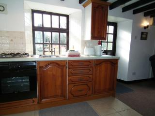 The well equipped kitchen has a full size oven, hob, microwave, and fridge with freezer compartment.
