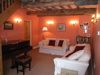 The sitting room with its original beams and baby grand piano