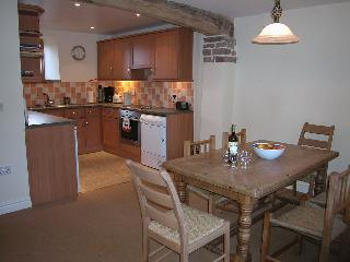 The kitchen/dining area has a solid pine table and seating for 6