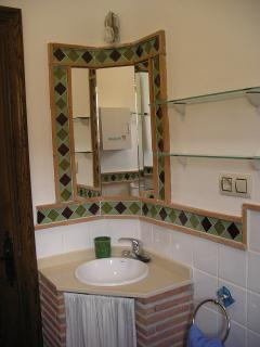 The family shower room with  local mosaic tiles includes hand rails and shower seat