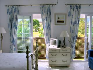 The master bedroom is a bright airy place to relax and watch the golfers playing their opening shots