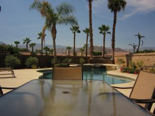 Patio table and chairs overlook the pool and mountains beyond
