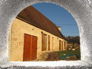 La façade, au travers de la cheminée du barbecue
