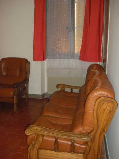 chambre 2 de 21m2 avec vue sur patio, lit double et ensemble en cuir de 2 fauteuils et un canapé