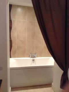Alcove bath in family bathroom.
