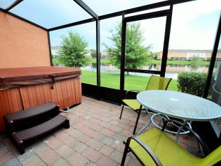 screened rear patio with hot tub and lake view.