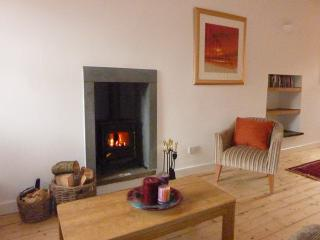 Sit  by a real log burner, in a cosy lounge