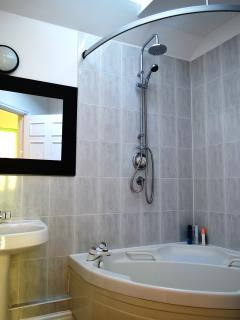 Ample bathroom with corner bath and overhead shower.