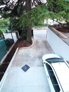 Secured private parking. Sliding garage doors are behind the pine tree