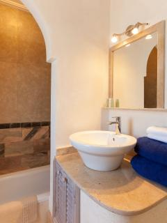 Second bathroom with a sunken bathtub set in local mica and marble