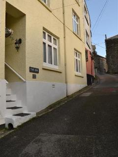 The exterior of The Den along a quiet lane in East Looe