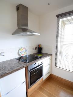 Kitchen with ceramic hob, electric oven, fridge with freezer compartment, sink and washing machine