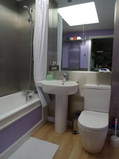 Modern bathroom with toilet, washbasin, bath and shower.