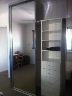 Inside the built in wardrobe, there is plenty of shelving, drawers and hanging space.
