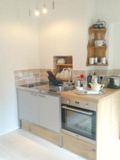 Kitchen area in The Engine Room with oven, hob, toaster, kettle, coffee machine and fridge