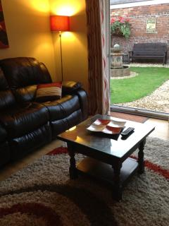 Comfortable tv lounge leads directly onto garden via patio doors-great for gatherings