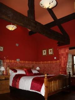 The master bedroom with its imposing oak beams,romantically decorated for that special get away.