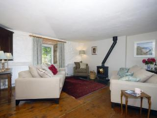 Holiday home near the sea at Ceibwr, Pembrokeshire - lounge with open fire and dining area