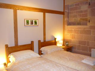 Twin Bed room with vaulted ceiling, exposed stone & brick walls, lovely oak quality flooring