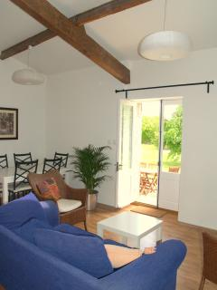 The bright, open living room/dining room with french doors leading onto the garden