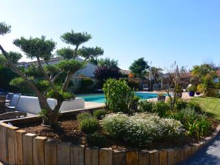 Landscaped gardens surround the pool area.