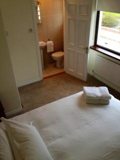 Bedroom 1 with view of ensuite shower and toilet