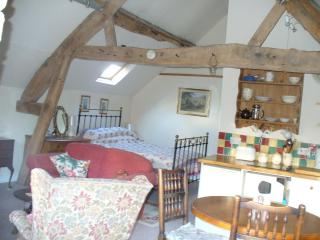 how the flat looks as you come in, showing the antique brass bed and the original old beams
