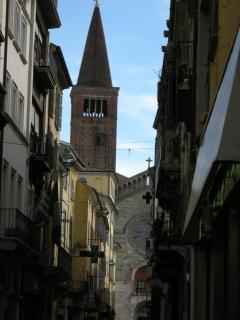 A street and Cathedral tower in Piacenza, still with the cage set high up in the wall, read the Magu