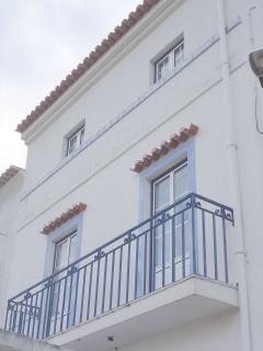 Facade of house with balcony on the 1st floor and windows on 2nd floor