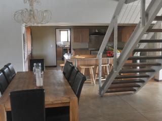 Interior from front door , dinning room and kitchen in background and stairs leading to viewing deck