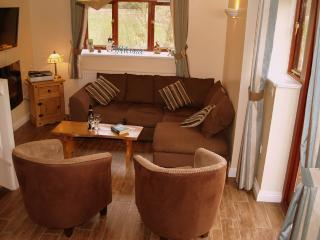 Open plan living room with 32' wide screen TV on wall and electric 'glow' fire for cosy evenings in