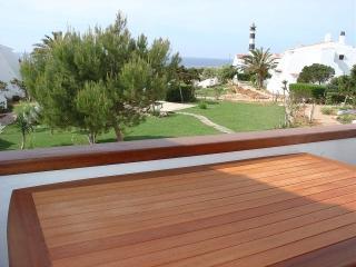 Vista al exterior desde la terraza con vistas al faro y al mar, jardin y piscina