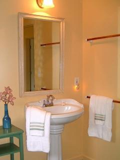 Pedestal sink under a large mirror